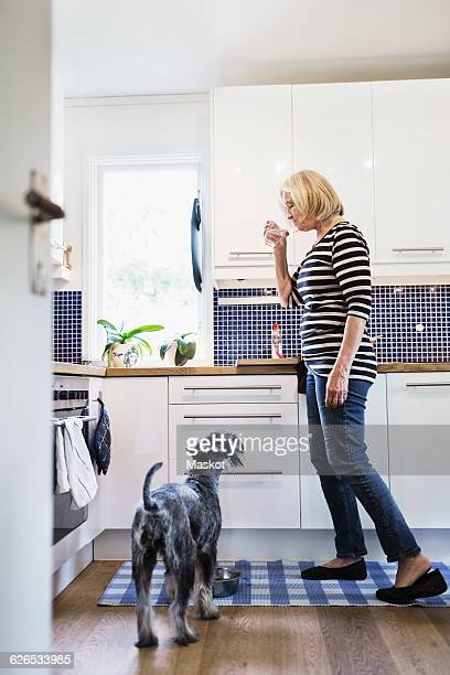 Senior woman drinking water while standing by dog in kitchen