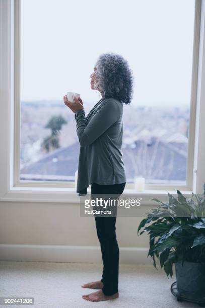 A Senior Ethnic Woman Drinks Tea While Contemplating the Day Ahead