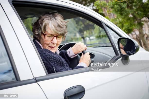 senior vrouw bestuurder draait zich om als ze keert haar auto - terugtrekken stockfoto's en -beelden