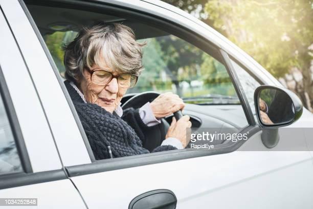 senior vrouw stuurprogramma draait om te keren, grimassen - terugtrekken stockfoto's en -beelden
