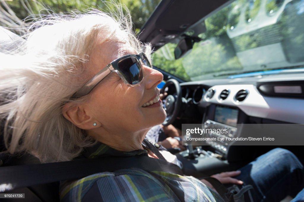 Senior woman driving in convertible : Stock Photo
