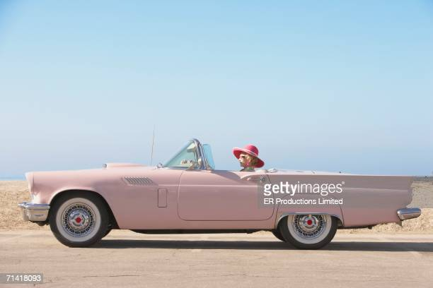 senior woman driving pink convertible - nevada stock pictures, royalty-free photos & images