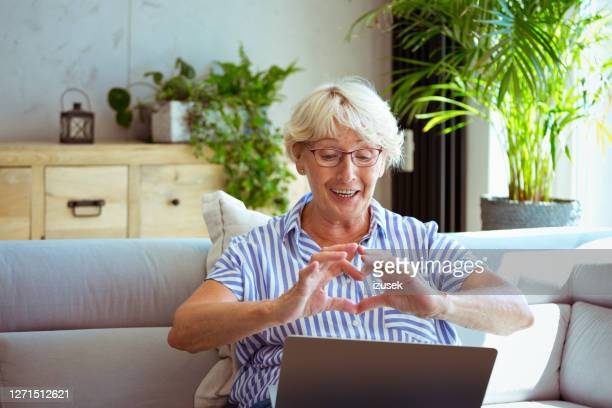 idosa durante chamada de vídeo - izusek - fotografias e filmes do acervo