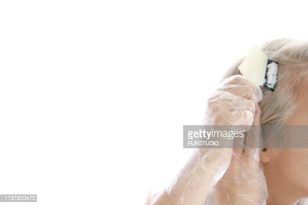 senior woman dyeing her hair - färbemittel stock-fotos und bilder