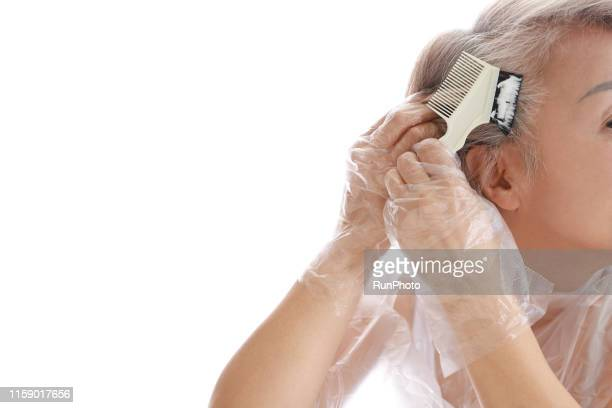 senior woman dyeing her hair - dye stock pictures, royalty-free photos & images