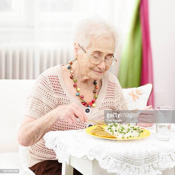 Senior woman eating at home