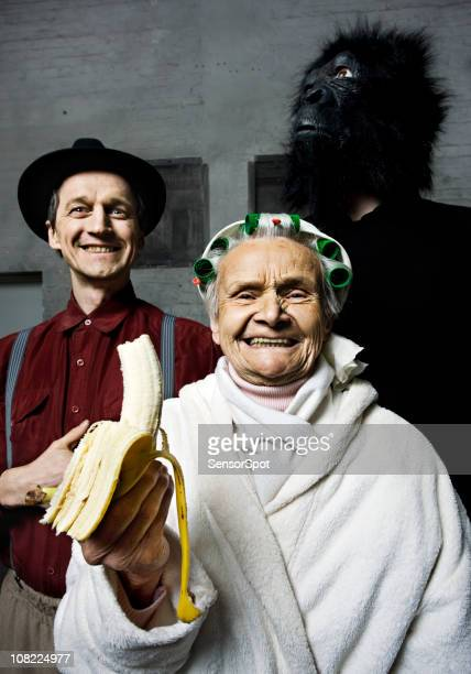 Senior Woman Eating Banana with Gorilla Man