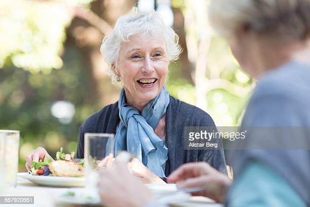 senior woman eating lunch - senior lunch stock photos and pictures