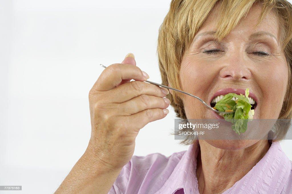 Senior woman eating salad : Photo