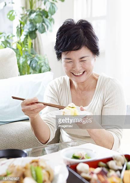 Senior woman eating sushi