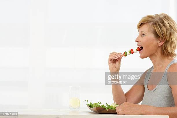 senior woman eating vegetable kebab - vegetable kebab stock pictures, royalty-free photos & images