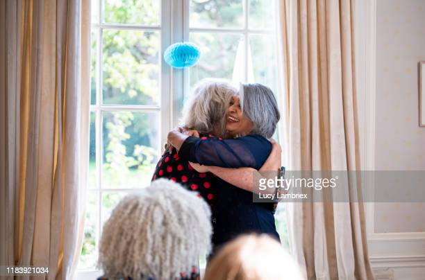 senior woman embracing her 65 year old friend for her birthday - receiving stock pictures, royalty-free photos & images