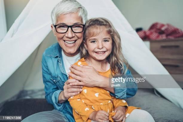 donna anziana che abbraccia sua nipote - capelli corti foto e immagini stock