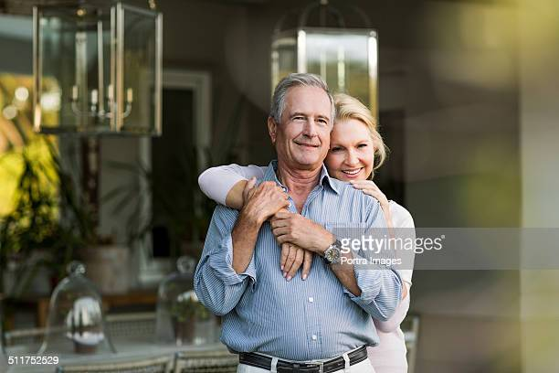 Senior woman embracing man at porch