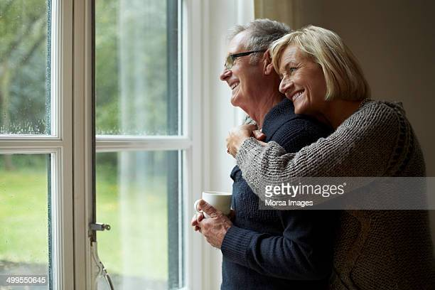 senior woman embracing man in front of door - love emotion stockfoto's en -beelden