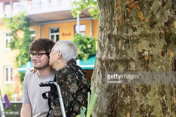 Senior woman embracing young man at tree
