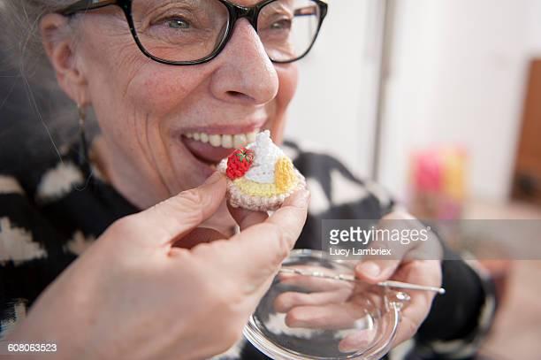 Senior woman enjoying a crafted cake