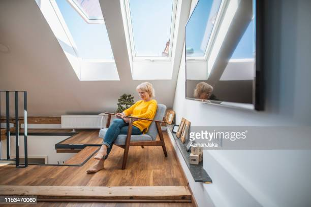 senior woman enjoying alone time with her digital tablet in a cozy nook - nook architecture stock pictures, royalty-free photos & images