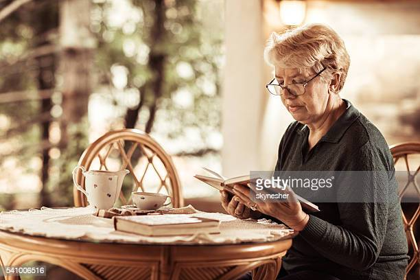 Senior woman enjoying at the terrace with a book.