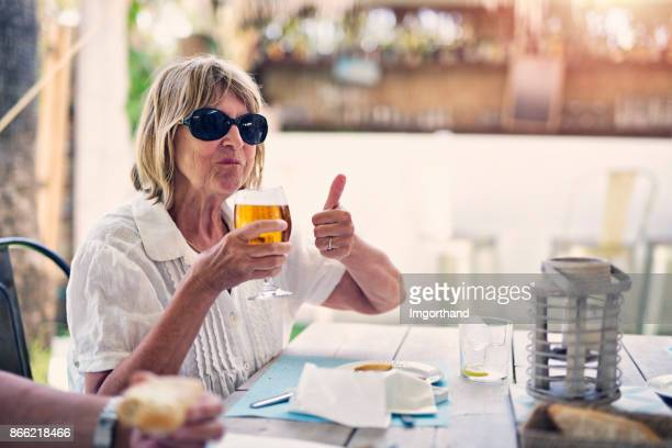 senior woman enjoying beer in restaurant - hot spanish women stock pictures, royalty-free photos & images