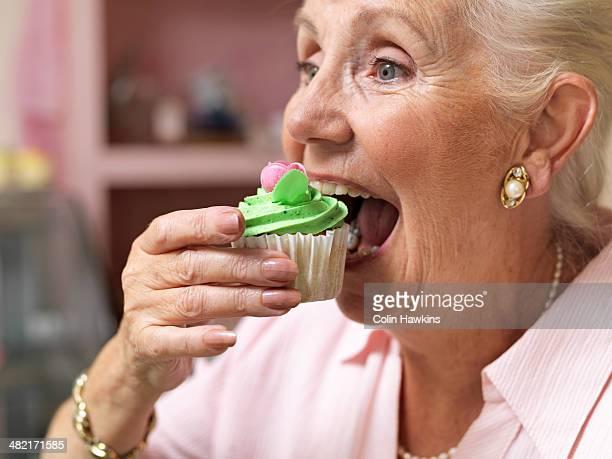 Senior woman enjoying cupcake in cafe
