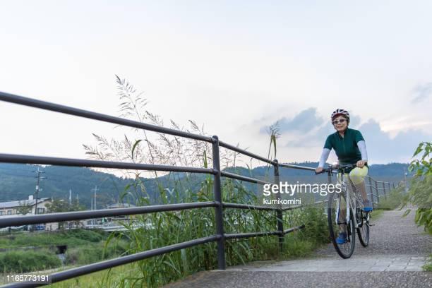 サイクリングを楽しむシニア女性 - 里山 ストックフォトと画像