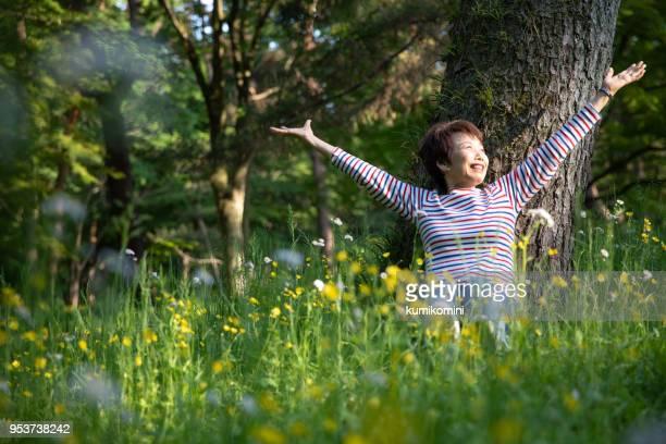 庭で早春を楽しむ年配の女性 - 息を止める ストックフォトと画像