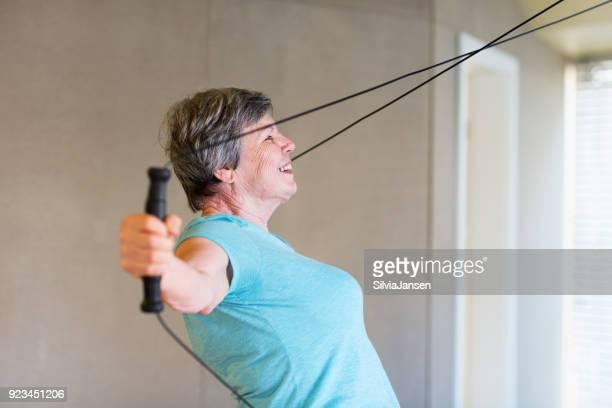 senior woman enjoying exercising in gym at machine