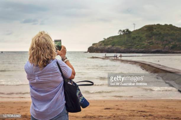 Senior woman enjoying free time in nature taking pictures of the landscape