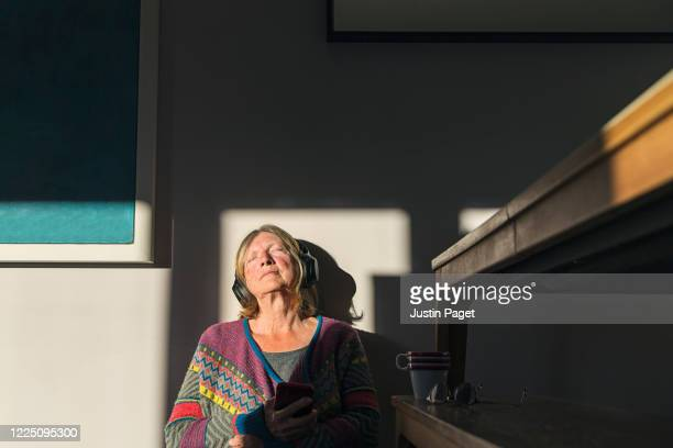senior woman enjoying some music with the sun on her face - domestic room stock pictures, royalty-free photos & images