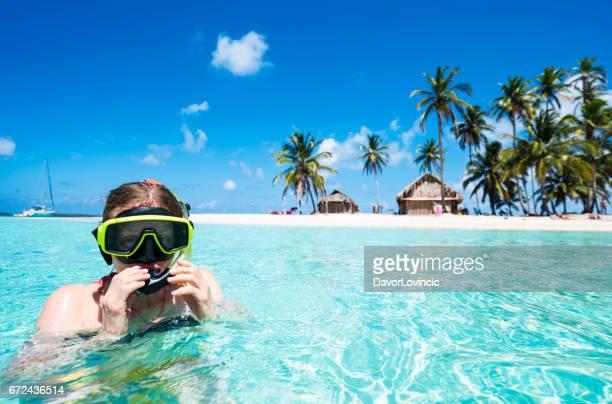 Senior vrouw genieten van zwemmen met scuba masker in de buurt van Isla de Perro eiland in het Caribisch gebied zien