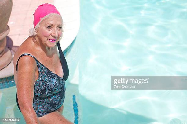 senior woman enjoying swimming pool at retirement villa - old woman in swimsuit stock pictures, royalty-free photos & images