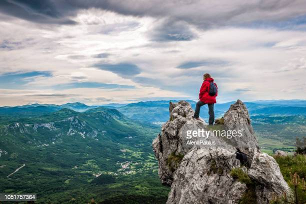 senior woman enjoying the amazing landscape high in the mountains - summit stock pictures, royalty-free photos & images