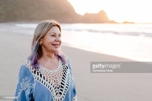 senior woman enjoying the beach while looking the ocean view - purple hair stock pictures, royalty-free photos & images