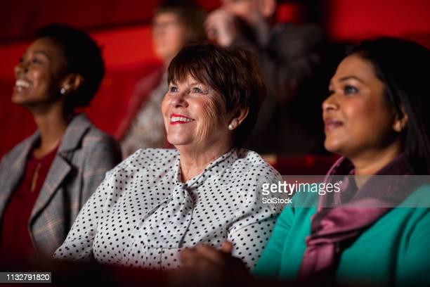 senior woman enjoying the movies - cinema stock pictures, royalty-free photos & images