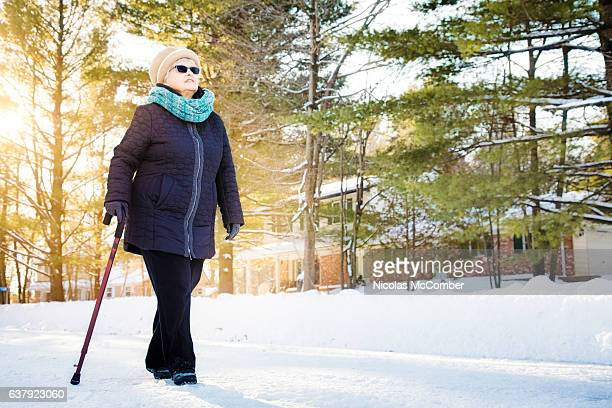 senior woman enjoying walk with cane in winter suburb - walking cane stock photos and pictures