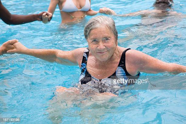 Senior woman enjoying water aerobics with young people