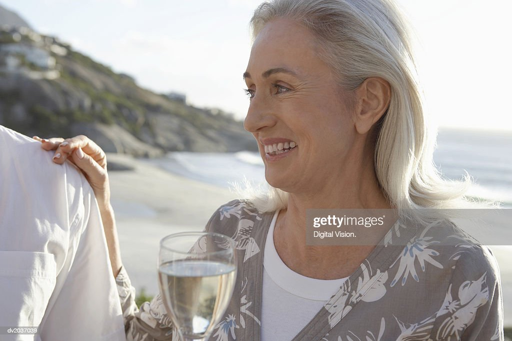 Senior Woman Enjoying White Wine on a Beach : Stock Photo
