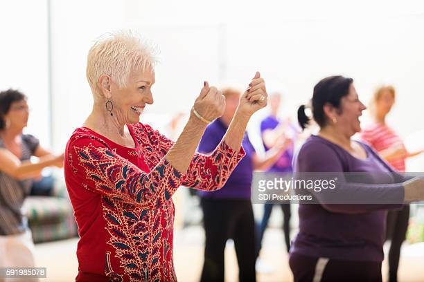 senior woman enjoys dance class - dancing stock pictures, royalty-free photos & images