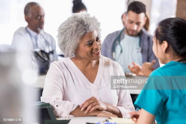 mulher sênior goza de discussão com a enfermeira da clínica gratuita - gratis - fotografias e filmes do acervo