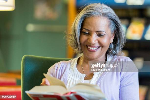 Senior woman enjoys reading in the library