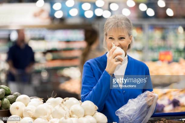 senior woman enjoys shopping for onion at grocery store - megastore stock photos and pictures