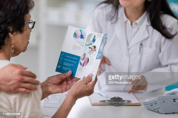 senior woman examines pharmacy brochure - brochure stock pictures, royalty-free photos & images