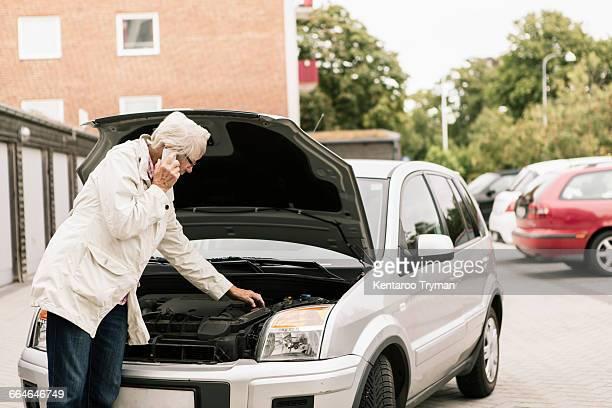 Senior woman examining car engine while using phone at roadside