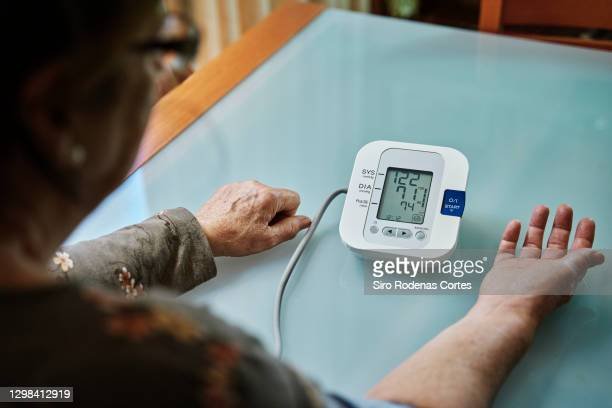 senior woman  examining her blood pressure on her arm - healthcare stock pictures, royalty-free photos & images