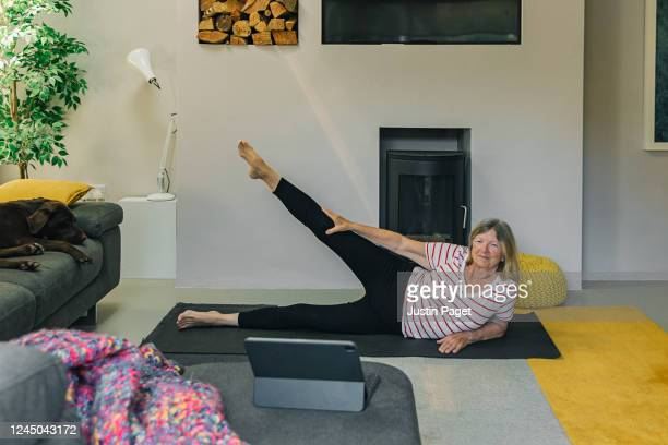 senior woman exercising at home - the internet stock pictures, royalty-free photos & images