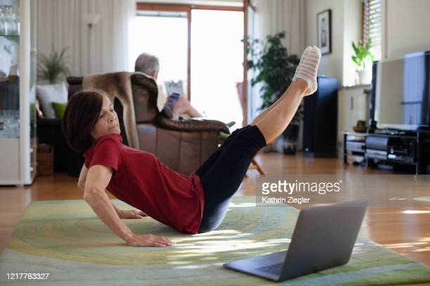 senior woman exercising at home, using laptop to follow online tutorial - relaxation exercise stock pictures, royalty-free photos & images