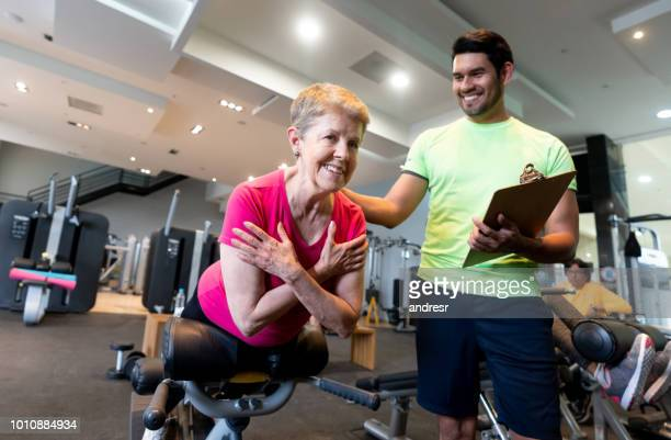 senior woman exercising at the gym with a personal trainer - fitness instructor stock pictures, royalty-free photos & images