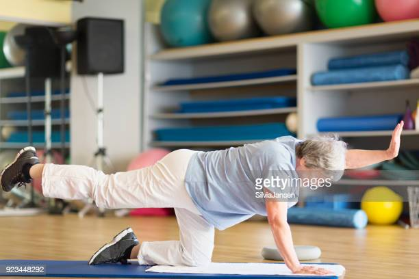 senior woman exercising in gym on mat - fat old lady stock photos and pictures