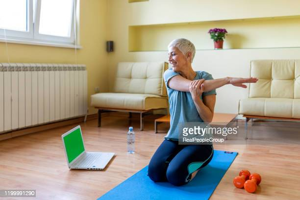 senior woman exercising in home gym. - net sports equipment stock pictures, royalty-free photos & images